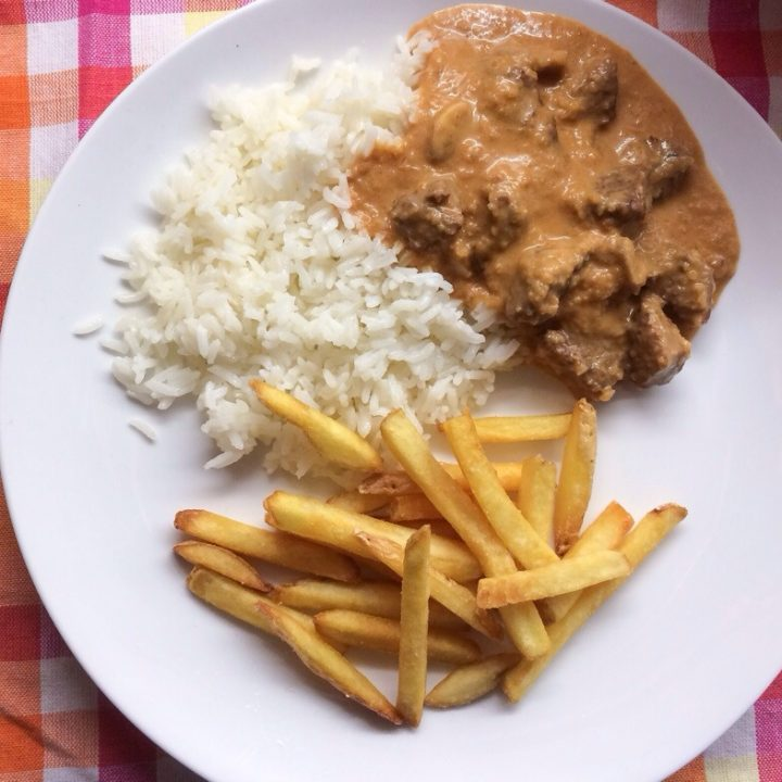 A plate of Brazilian beef stroganoff with fries and rice.