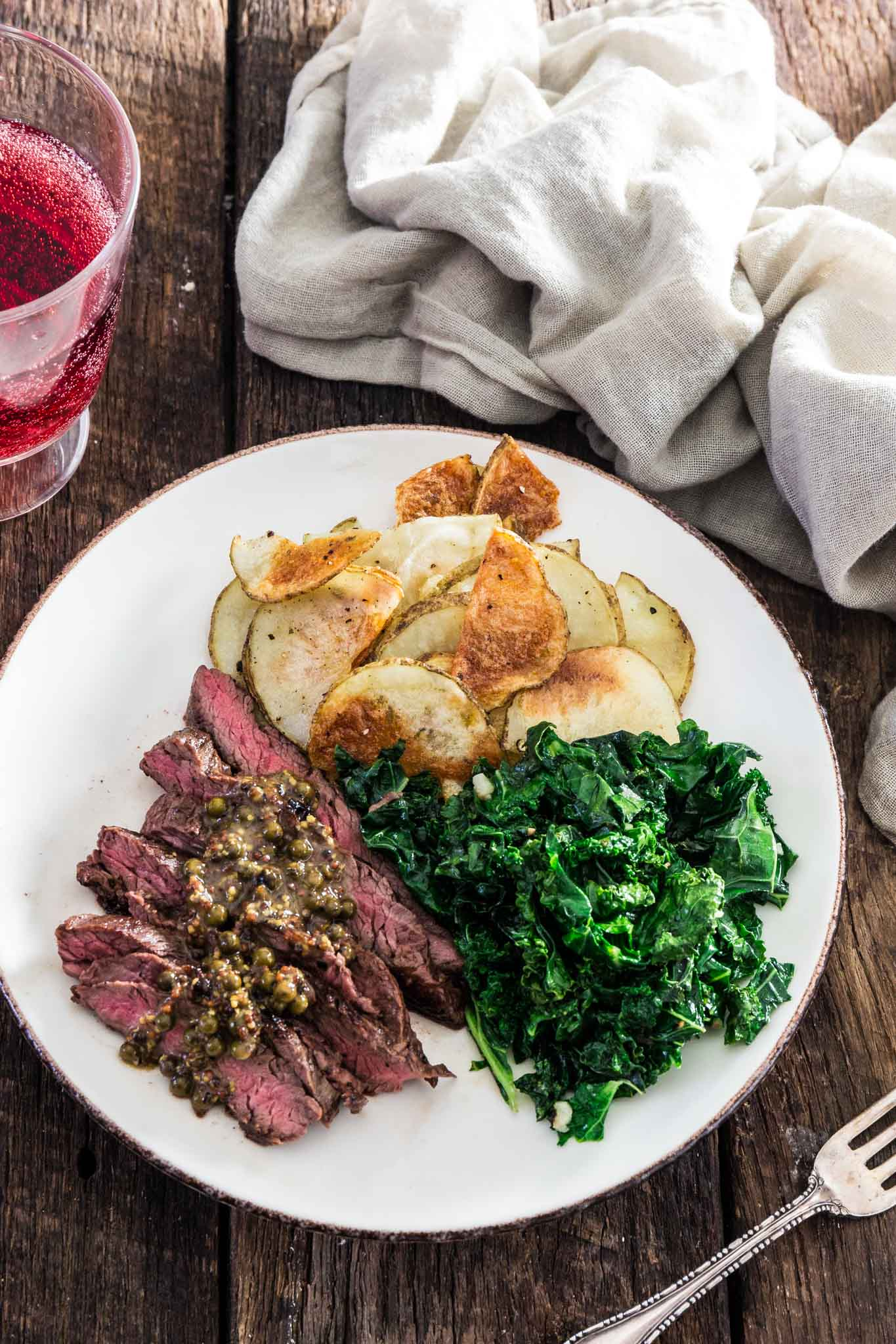Steaks with Green Peppercorn Sauce   www.oliviascuisine.com   If you're looking for an impressive meal that is easy enough to put together on a weekday, this Steak with Green Peppercorn Sauce is the answer! The steak is cooked to perfection and served with a silky mustard-y peppercorn sauce, kale and roasted potatoes.