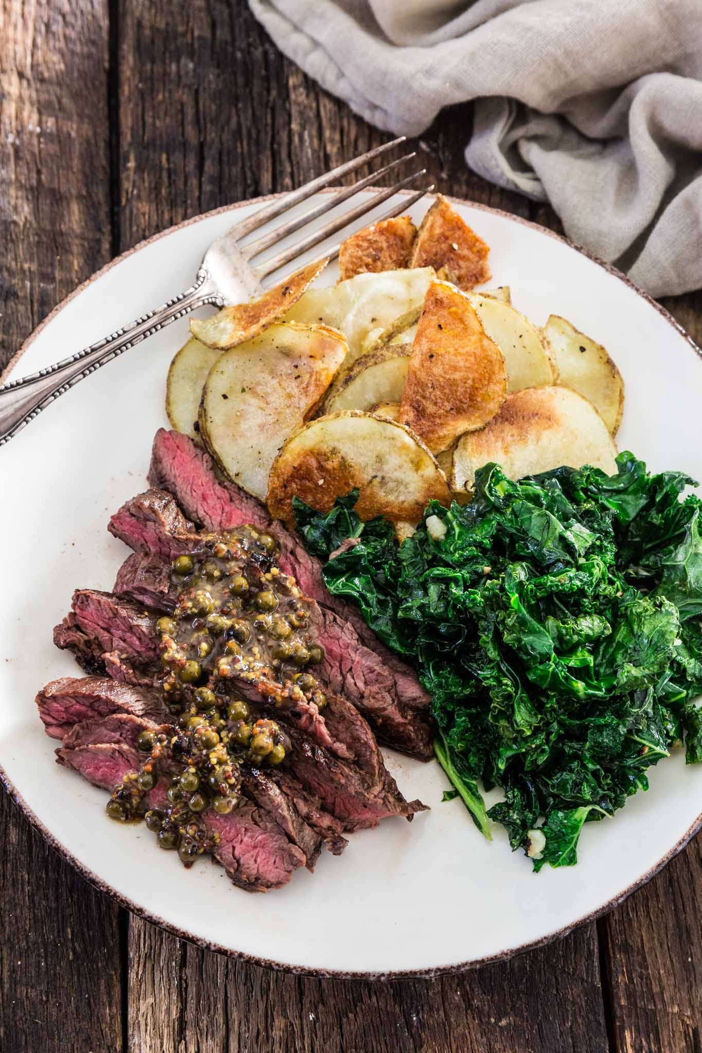 Steaks with Green Peppercorn Sauce | www.oliviascuisine.com | If you're looking for an impressive meal that is easy enough to put together on a weekday, this Steak with Green Peppercorn Sauce is the answer! The steak is cooked to perfection and served with a silky mustard-y peppercorn sauce, kale and roasted potatoes.