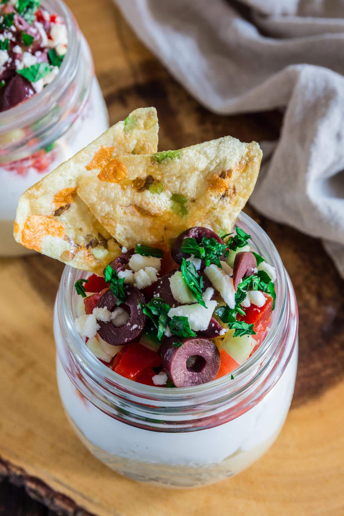 Seven Layer Mediterranean Dip | www.oliviascuisine.com | Light, healthy and perfect for entertaining during the warm weather, this Seven Layer Mediterranean Dip is filled with all the greek flavors we all love: hummus, Greek yogurt, veggies, feta and olives. I like to serve it in individual cups so it stays fresh and nobody needs to worry about double dippers! ? (Recipe by @oliviascuisine.)