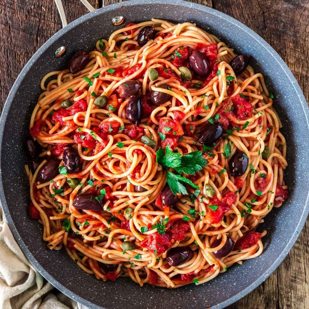 Spaghetti alla Puttanesca | www.oliviascuisine.com | Spaghetti alla Puttanesca is an Italian classic and a specialty of the Campania region. Consisting of tomatoes, garlic, olives, capers and anchovies (which are optional in my version), this dish is quick, deliciously aromatic and on the table in 20 minutes! (Recipe by @oliviascuisine.)