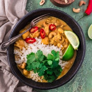 a bowl of thai yellow curry with rice, lime and chili peppers