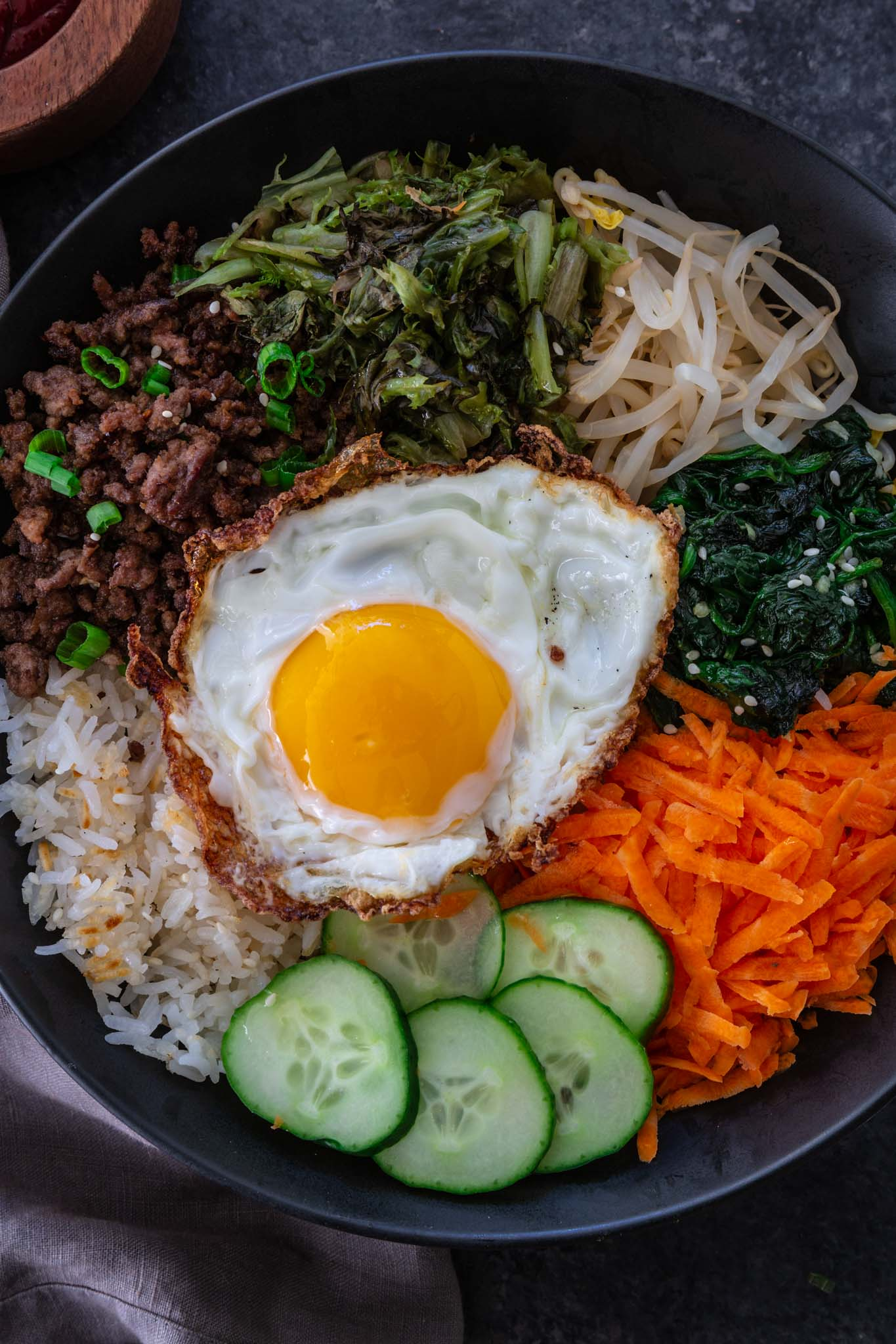 Bibimbap (Korean Beef Rice Bowl) | www.oliviascuisine.com | My version of Bibimbap, a popular Korean rice dish, takes a few shortcuts for convenience! The good news is that it's done in less than 30 minutes without compromising flavor. Serve with a fried egg on top for that extra wow factor! (Recipe and food photography by @oliviascuisine.)