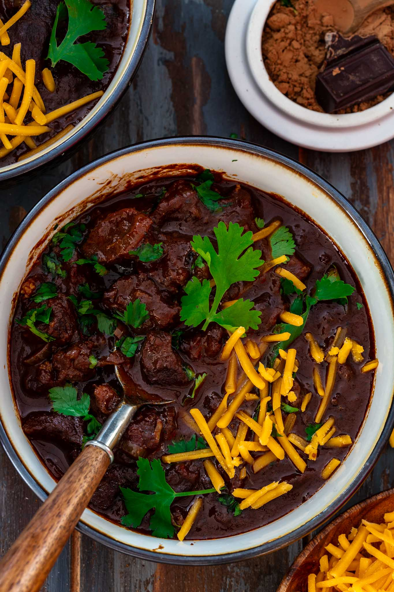 A bowl of beef chili topped with cilantro and cheddar cheese