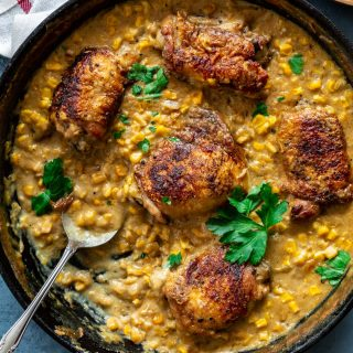 A cast iron pan with chicken thighs and creamed corn