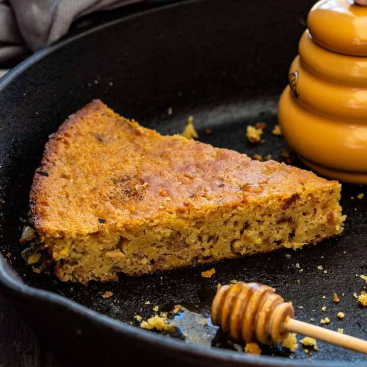 A slice of bacon cornbread with honey