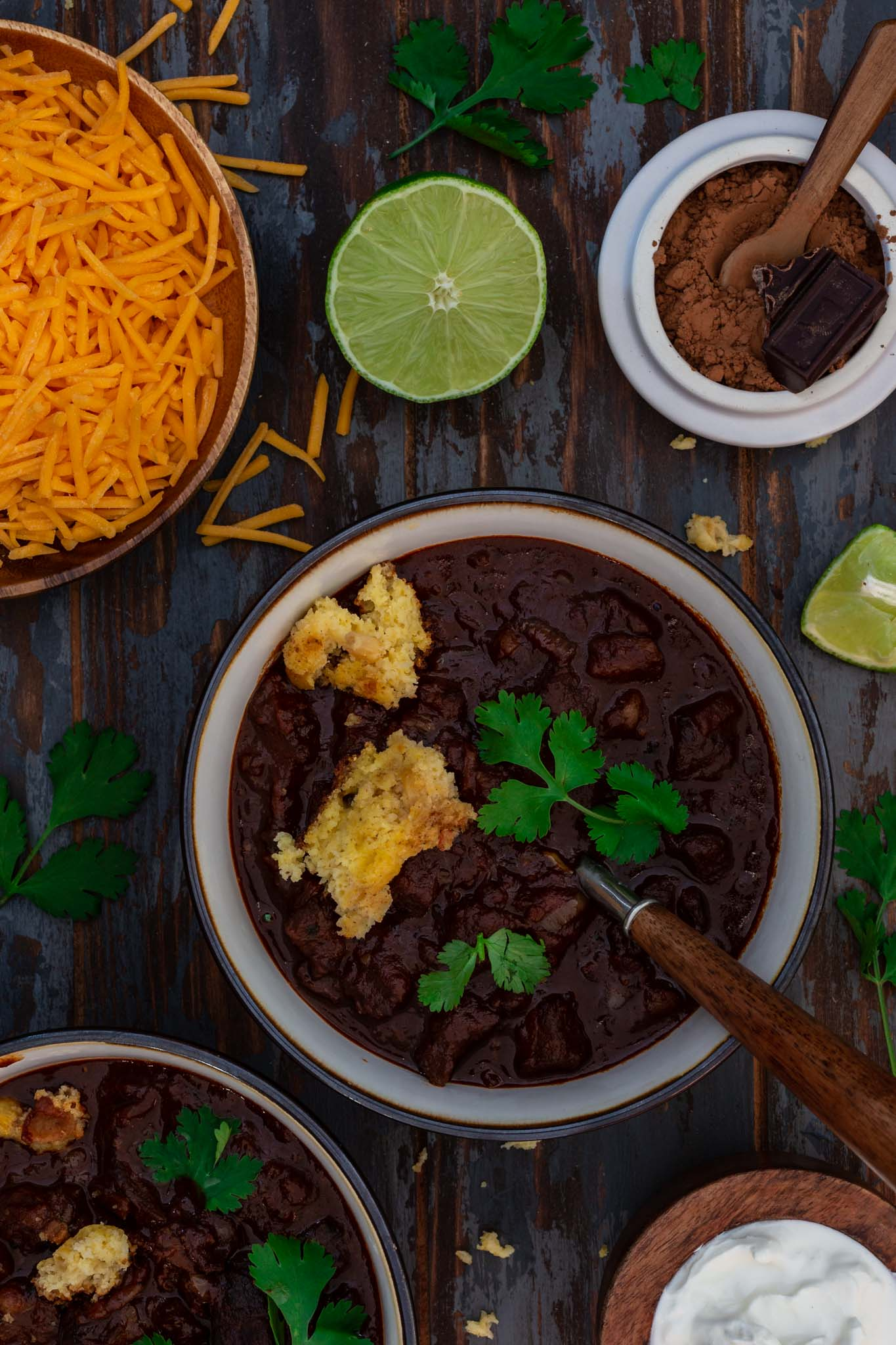 Two bowls of Double Chocolate Chili being served with cheddar cheese, sour cream and lime.
