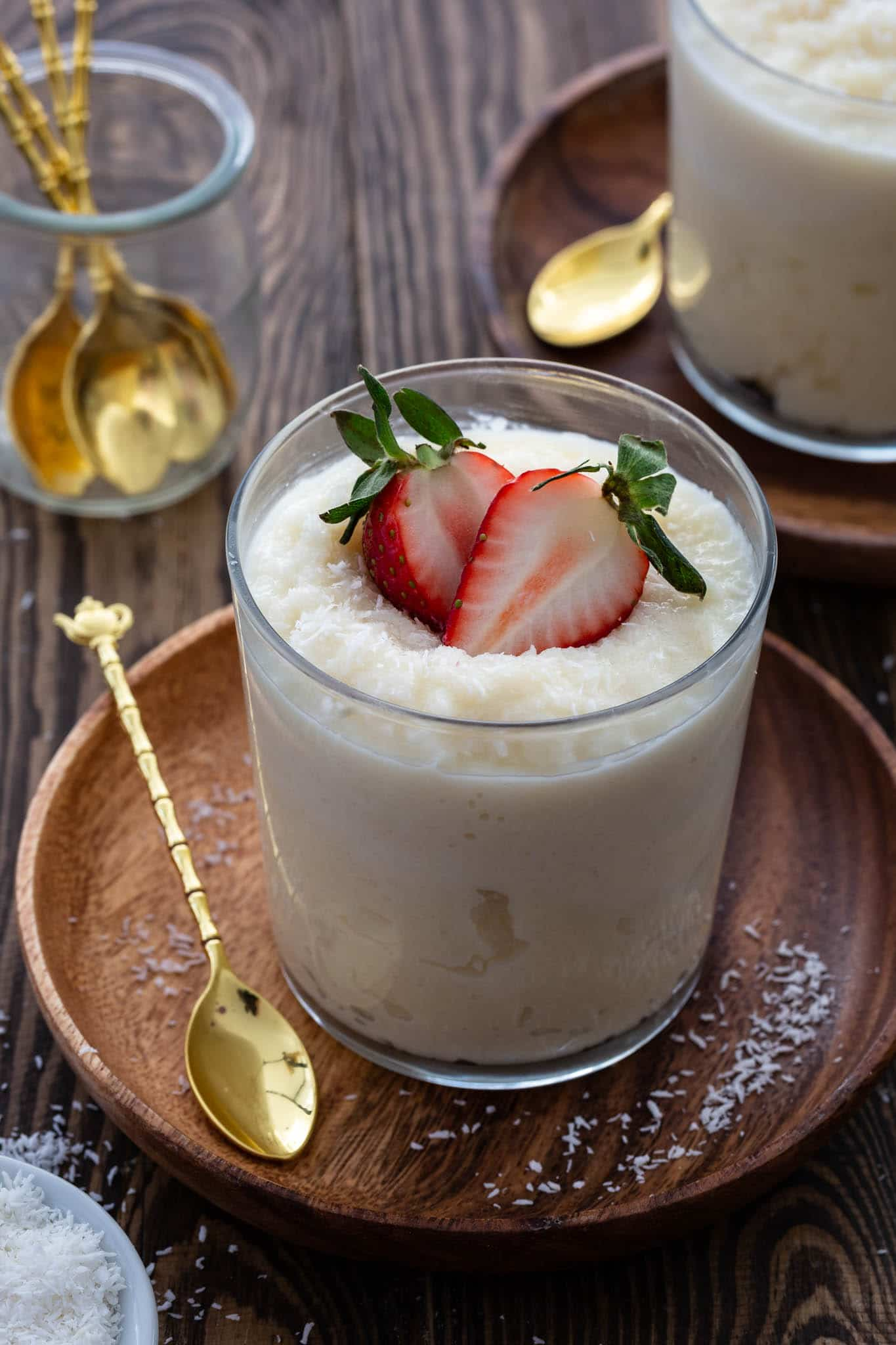 A glass of cocada cremosa (Brazilian coconut pudding) topped with fresh berries.