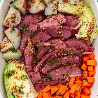 Sliced corned beef with cabbage, carrots and potatoes.