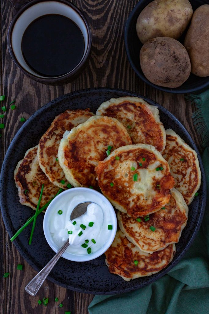 A plate of mashed potato pancakes, served with sour cream.