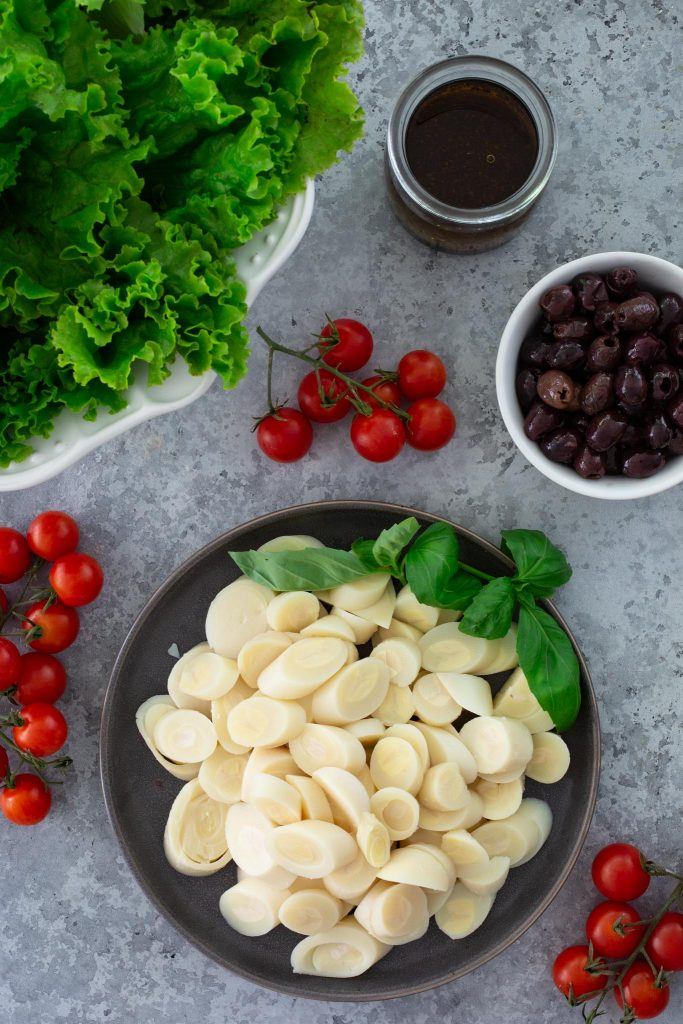 Ingredients for Brazilian salad with hearts of palm, cherry tomatoes, olives, lettuce and basil.