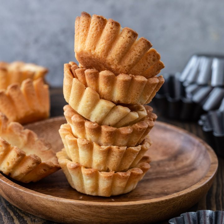 A pile of pâte sucrée tartlets.