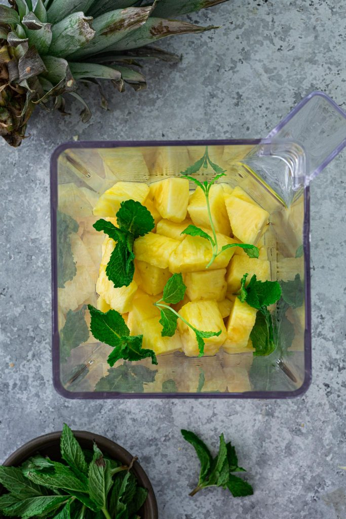 Chunks of pineapple and mint leaves in a blender.
