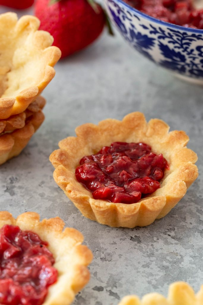 A tartlet shell filled with strawberry jam.
