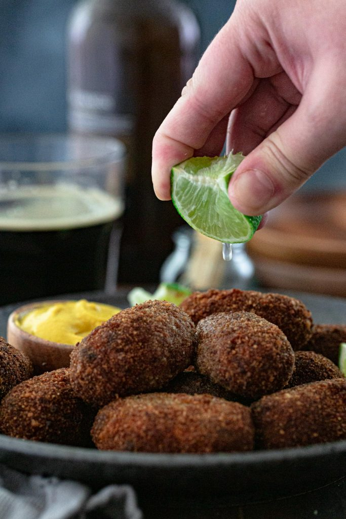 Squeezing a lime over beef croquettes