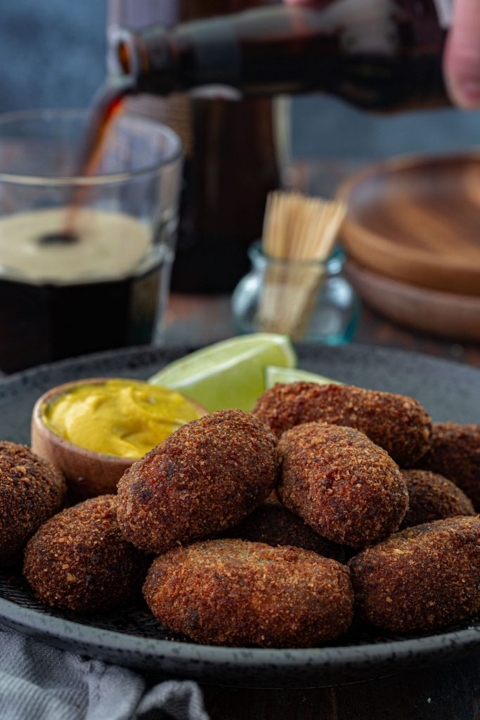 A platter of oxtail croquettes served with mustard and lime wedges.