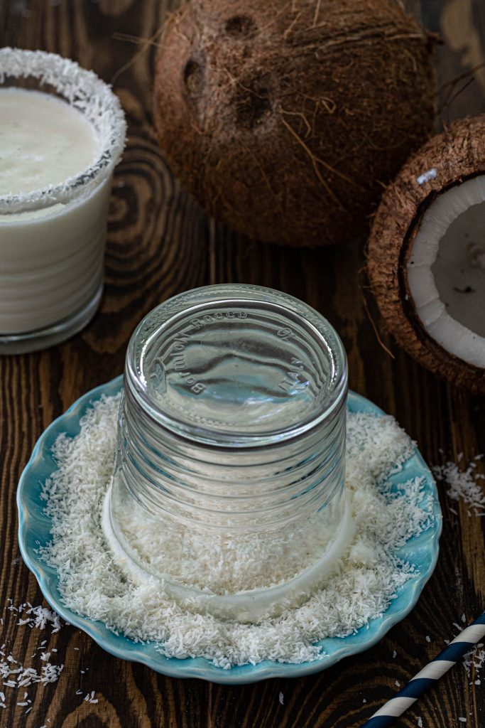 Rimming the serving glass with shredded coconut.
