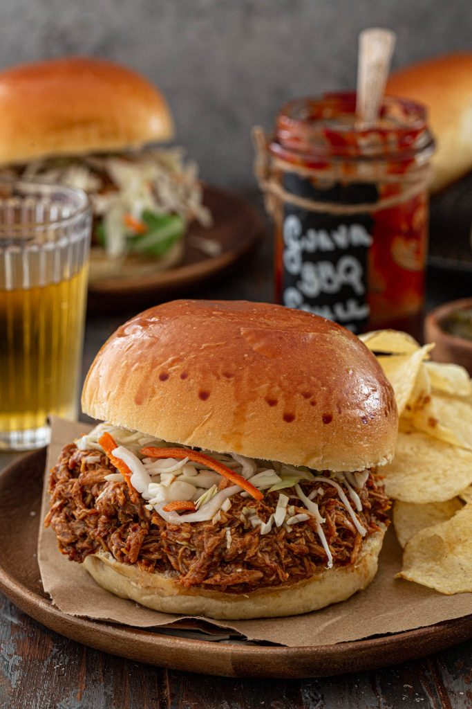 A sandwich made with Guava BBQ Pulled Chicken and cole slaw.