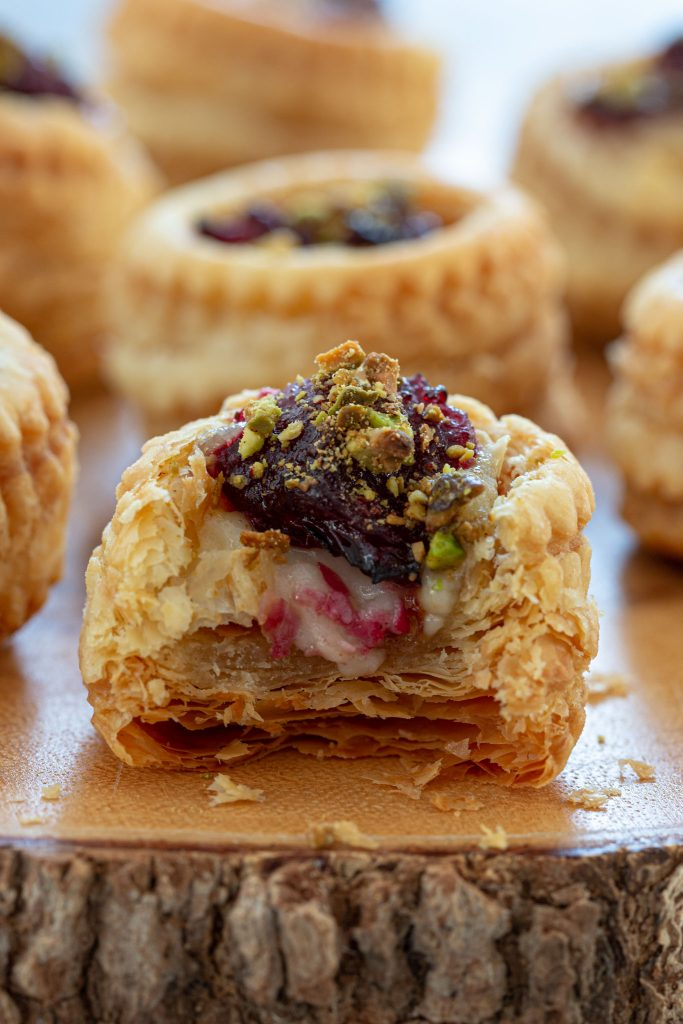Vol au Vent stuffed with brie and topped with cranberry sauce and crushed pistachios.