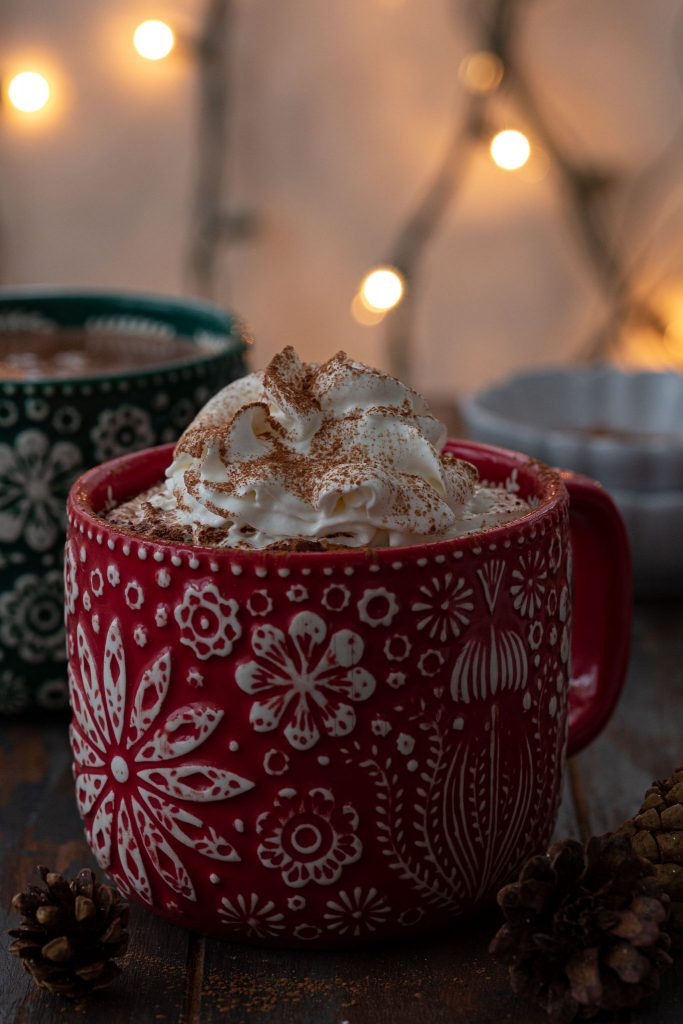 Creamy and thick hot cocoa topped with whipped cream and a sprinkle of cinnamon.