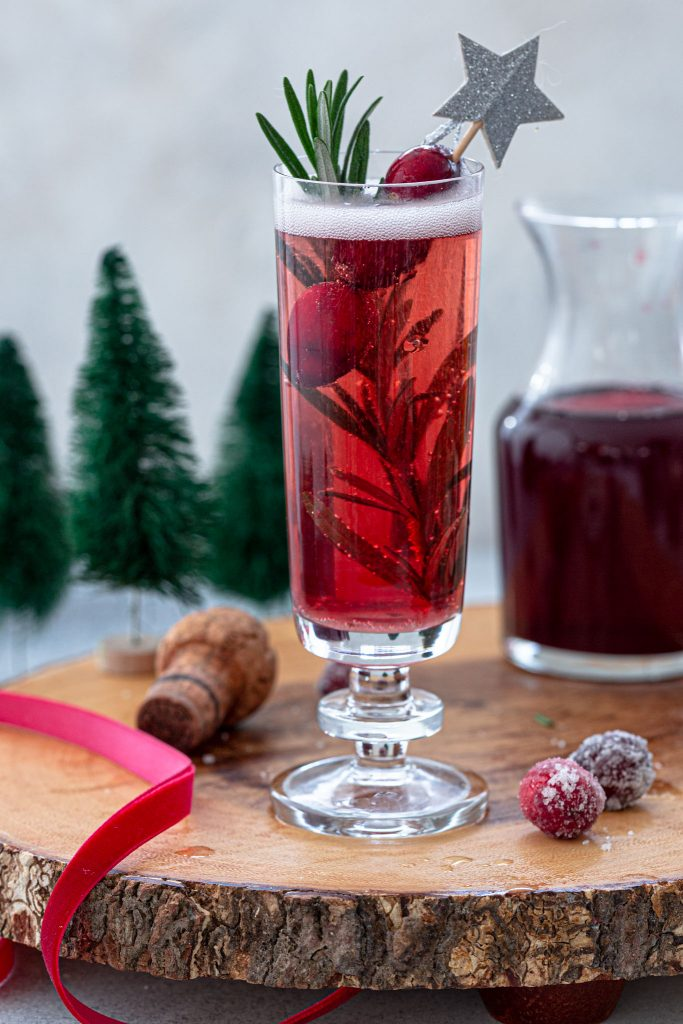 Christmas mimosa made with cranberry juice and rosemary.