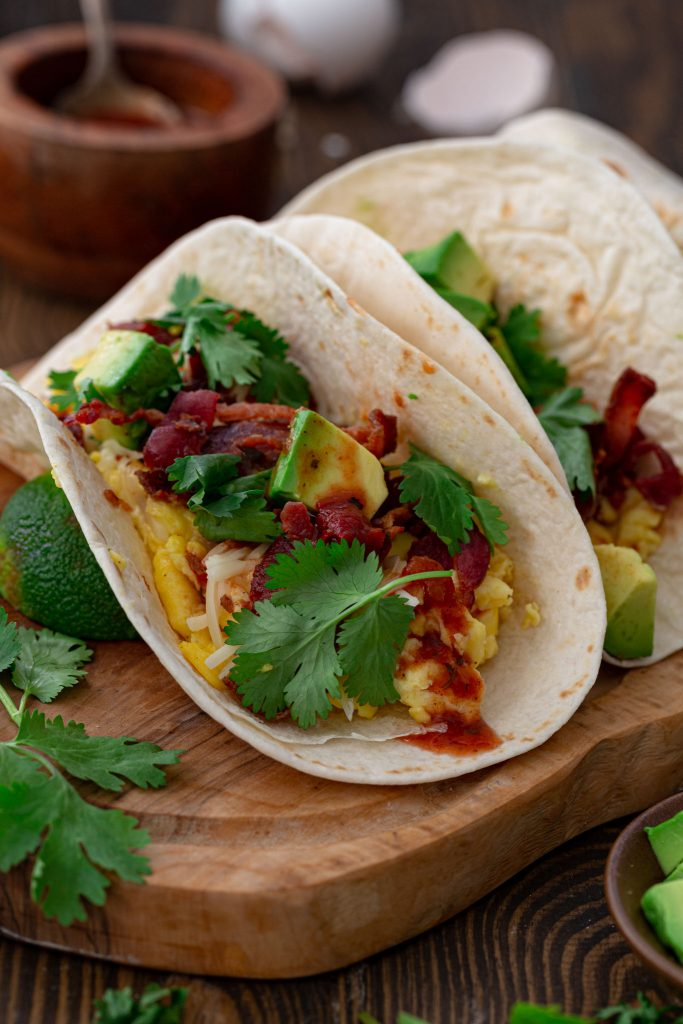 Low Carb Breakfast Tacos topped with avocados, salsa, cheese and cilantro.