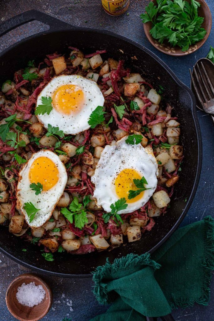 A cast iron skillet with corned beef hash and fried eggs
