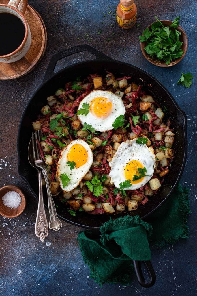 An overhead shot of corned beef hash with eggs.