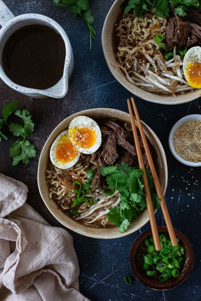 A bowl of short rib ramen soup topped with eggs, scallions, cilantro, bean sprouts and toasted sesame seeds.