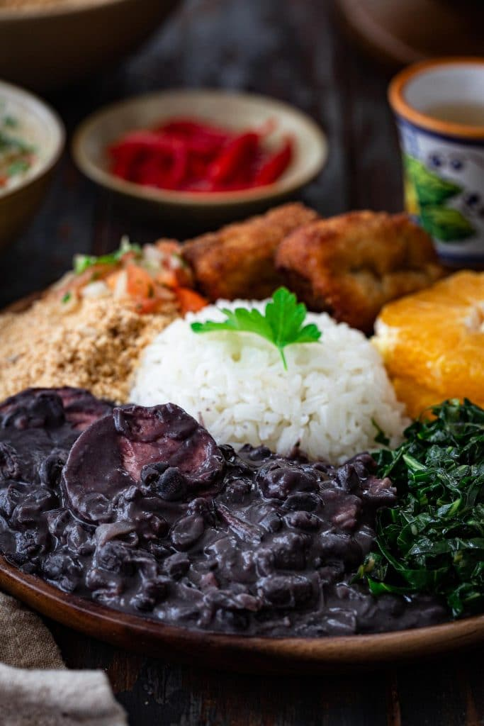 A plate of Brazilian black bean stew, rice, collard greens, oranges, farofa, fried bananas and salsa.