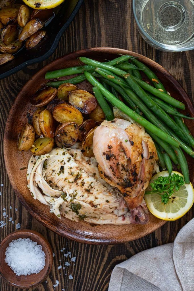 Roasted chicken dinner served with potatoes and green beans.