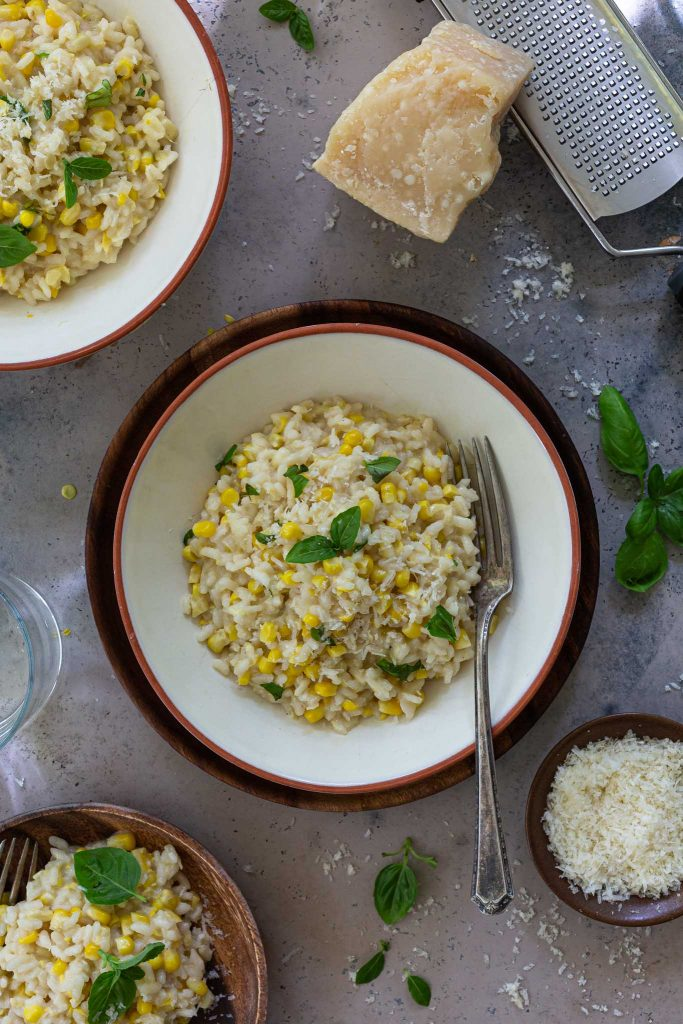 An overhead shot of fresh corn risotto in a bowl.