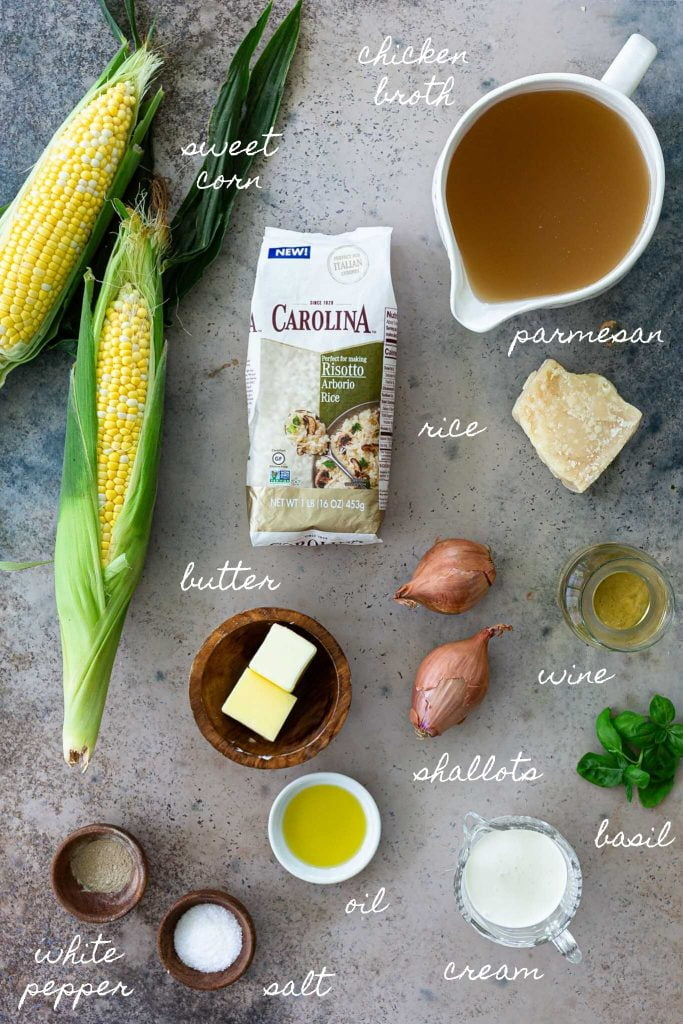A photo of all the ingredients: corn, arborio rice, broth, parmesan cheese, shallots, white wine, butter, oil, white pepper, salt, cream and basil.