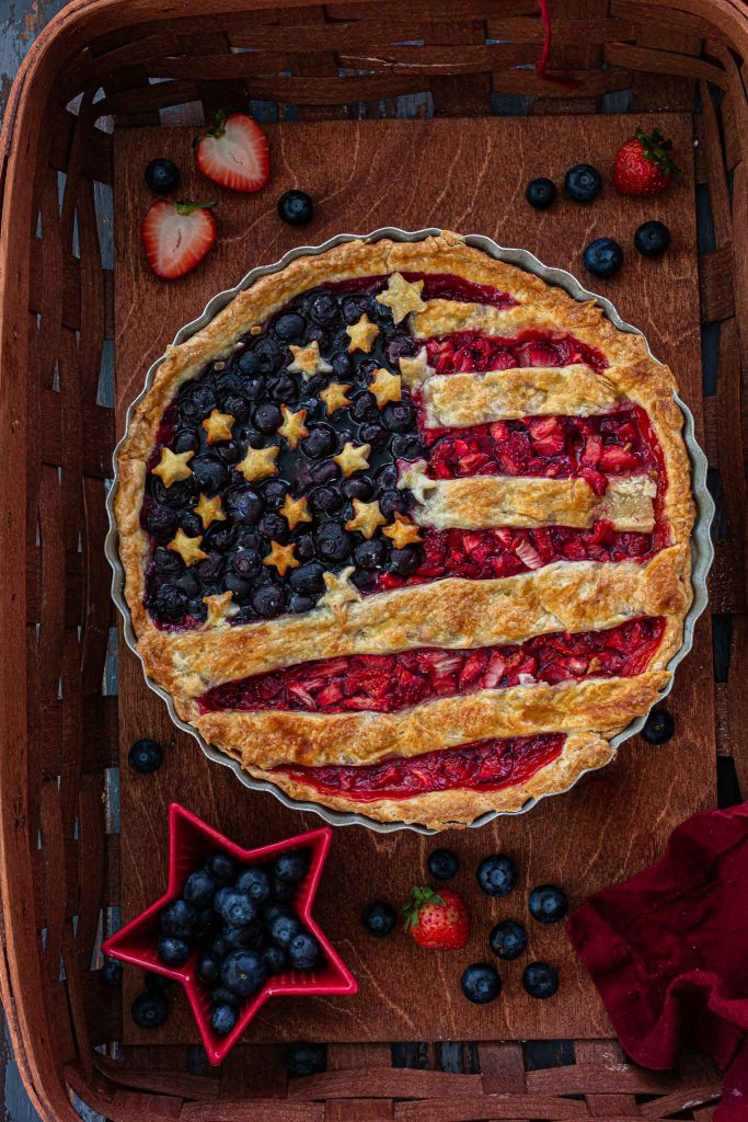 An overhead shot of an American flag berry pie inside a basket.