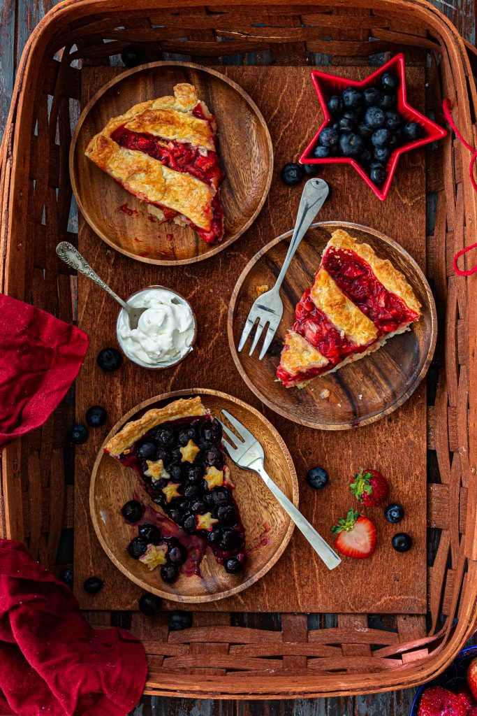 Three berry pie slices in a basket.