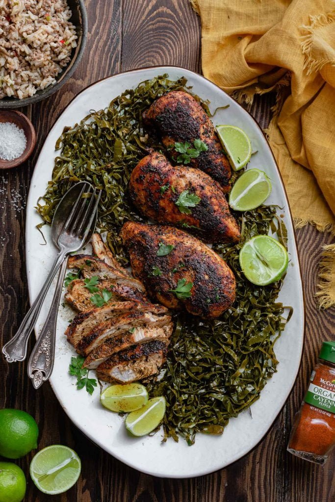 A platter of blackened chicken breasts over a bed of collard greens. You can see lime wedges and halves as a garnish, a bowl of dirty rice, a bowl of salt, a yellow napkin and a jar of cayenne pepper.
