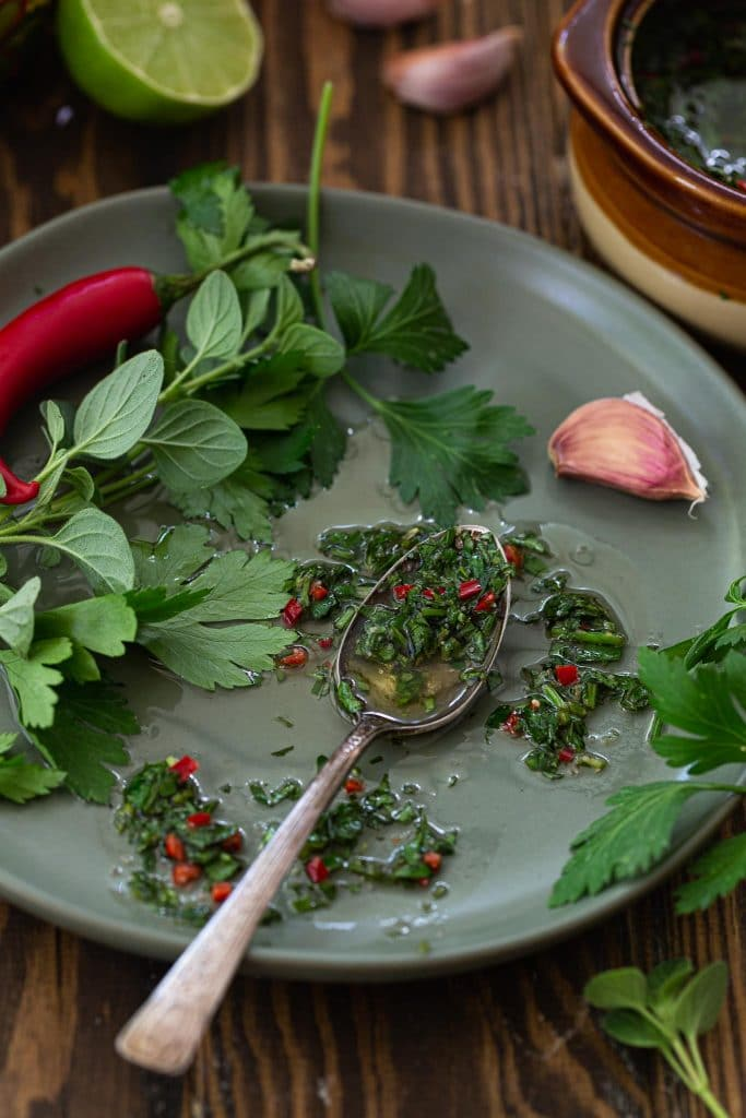 A plate with chimichurri, herbs, a garlic cloves and a chili pepper.