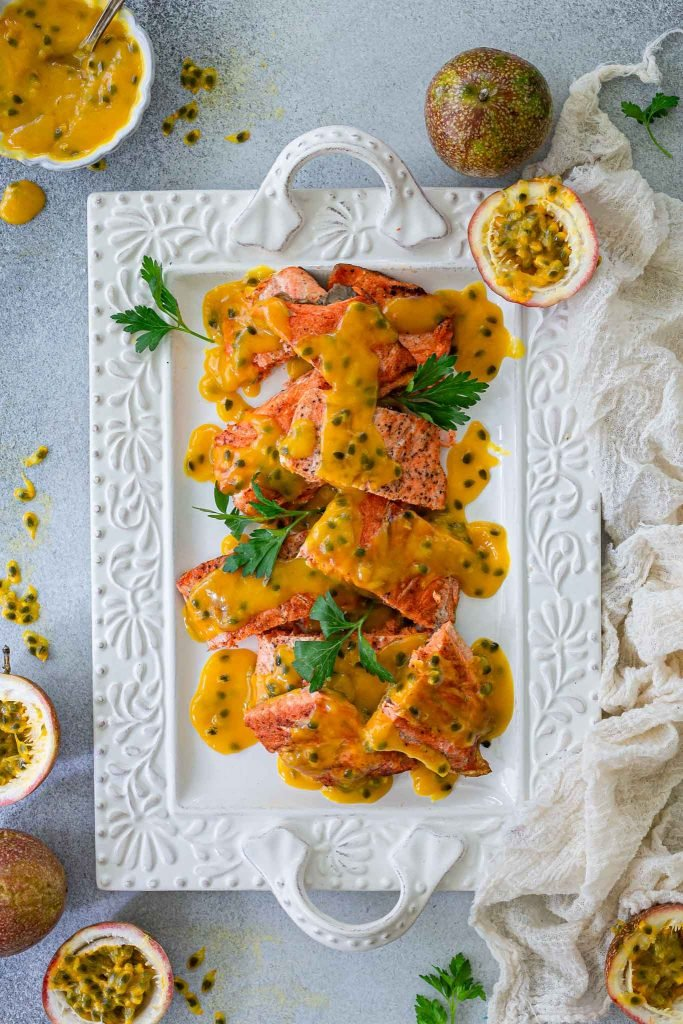 A platter with pan fried salmon with passion fruit sauce spooned on top.
