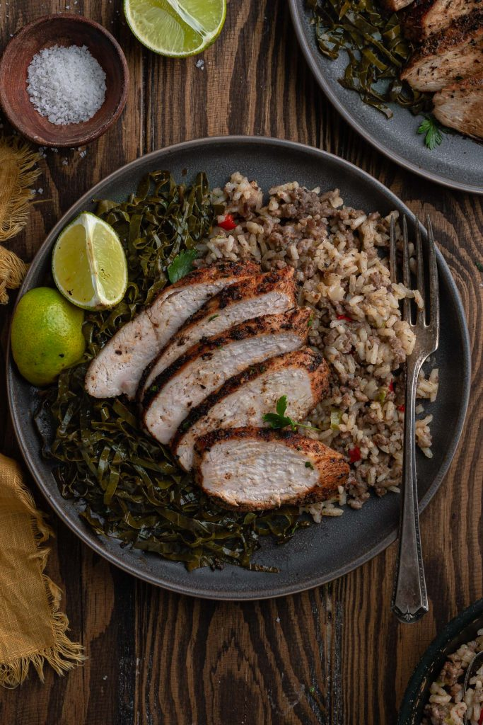 An overhead shot of one individual serving of the blackened chicken, dirty rice and collard greens.