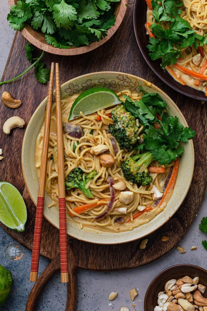 Closeup overhead photo of a bowl of Thai-inspired noodles, garnished with chopped cashews, lime wedge and fresh cilantro.