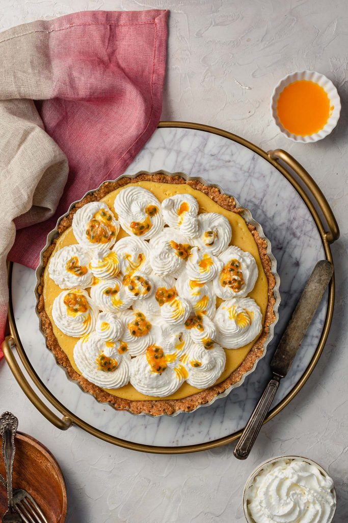 A passion fruit cream pie sits on a marble tray. You can also see a knife, a napkin, a bowl of whipped cream, a smaller bowl with passion fruit juice, plates and forks.