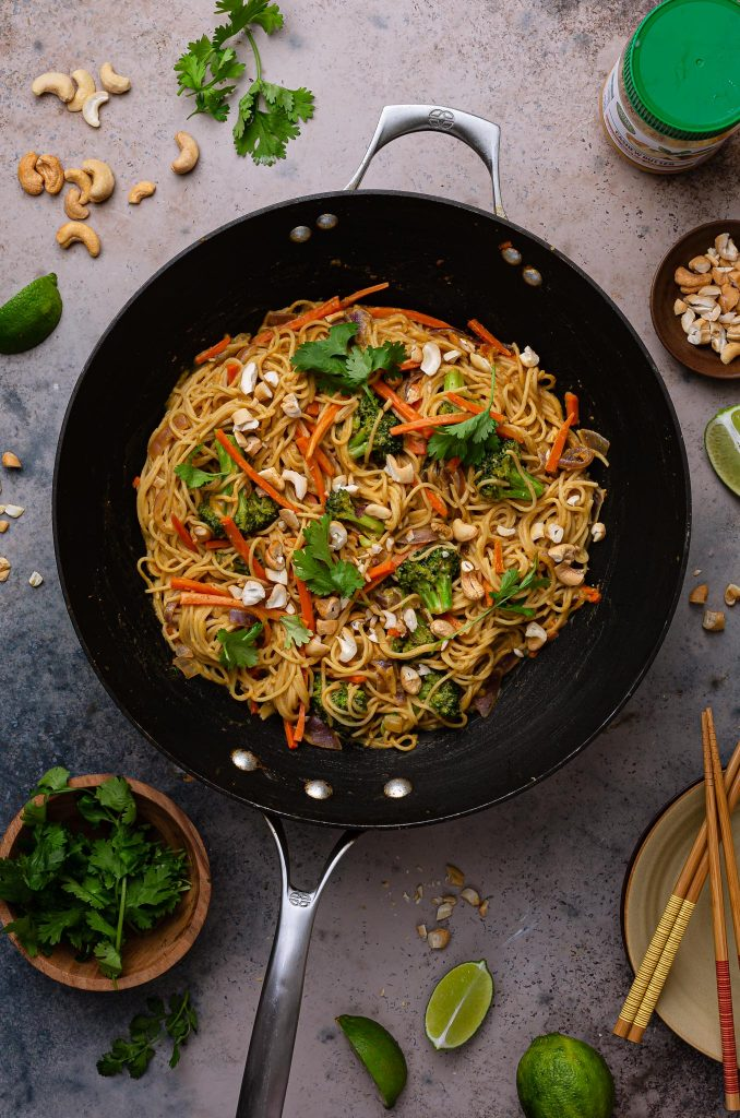 Curry noodles in the wok pan. Little bowls with garnishes can be seem on the table.