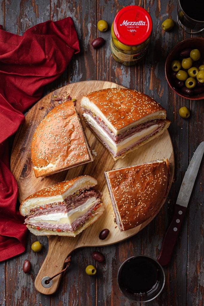 An overhead view of a Muffuletta sandwich, cut into 4 wedges.