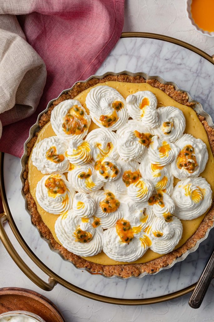 A close up shot of a whole passion fruit cream pie, decorated with dollops of whipped cream and fresh passion fruit pulp.