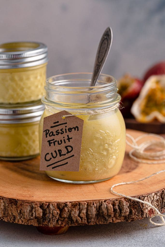A jar of passion fruit curd with a spoon inside. Two more jars and some passion fruit can be seen in the background.