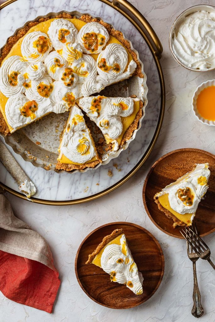 Two slices of the passionfruit cream pie in plates, and the cut pie.