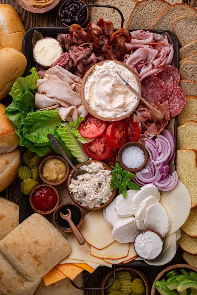 A build-your-own sandwich platter, with charcuterie, toppings, cheese and bread.