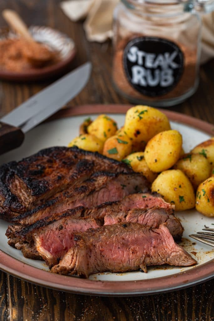 A perfectly cooked dry rubbed steak with baby potatoes. You can see a jar of steak rub in the background.