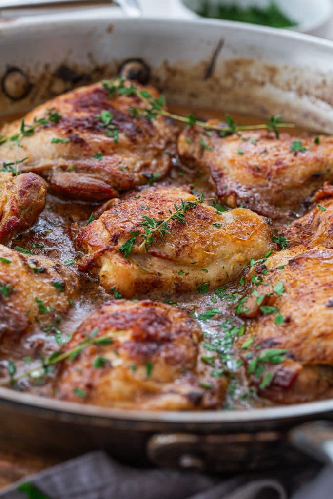 A skillet with French Mustard Chicken, garnished with thyme sprigs.