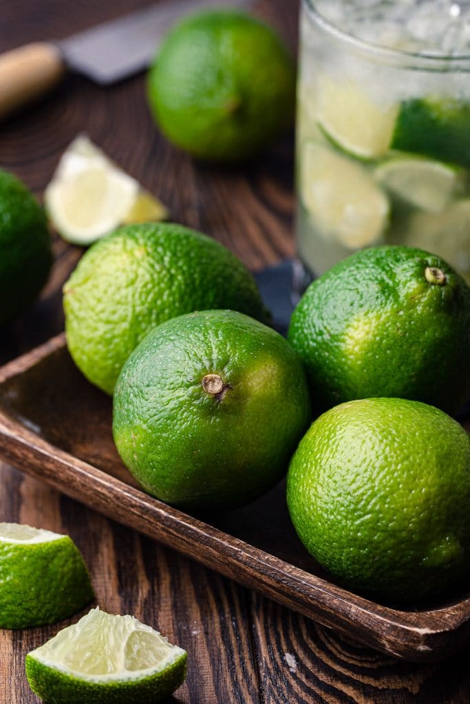 Four limes in a tray.